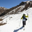 A lonely trekker hiking through snow high in mountains on a bright day — Foto Stock #56804795