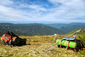 Two backpacks and trekking poles on a summit of a mountain — Foto Stock