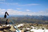 Trekking poles on a snowy summit of a mountain with a great view — Stock Photo