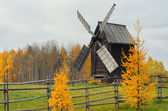 Windmill behind a fence in rural area neaby forest — Stock Photo