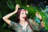 Hippie-girl with tropical flower in her long hair smiling and winking — Stock Photo
