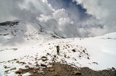 Trekker hiking through snow in mountains — Stock Photo