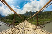 Suspension bamboo bridge across the river in a forest and rice fields — Stock Photo