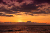 Amazing sunset featuring volcano and sea under awesome cloudy sky — Stock Photo