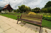 View to the path with few benches through the garden featuring traditional Thai temples, flowers and monuments — Stock Photo