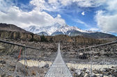 Suspencion bridge across the mountain river in Himalayas — Stock Photo