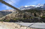 Suspension bridge across the river in mountains — Stock Photo