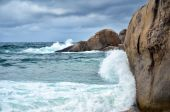 Wave crashing against stones at the rocky beach — Stock Photo
