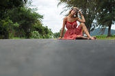Young hippie girl sitting on the road — Stock Photo