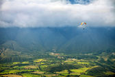 Paragliding in mountains above fields and villages - view from air — Stock Photo