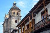 Bottom-up view to traditional balcony and Cathedral in Cartagena old town — Stock Photo