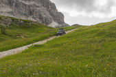 Dune buggy on a mountain trail in the green meadows, Dolomites, Veneto, Italy — Stockfoto