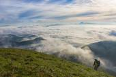 Hiker at sunrise over the clouds, mount Cucco, Apennines, Umbria — Stockfoto