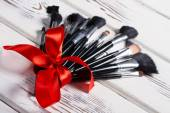 Makeup brushes tied of a red ribbon. — Stock Photo