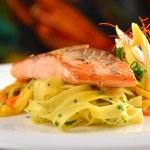 Grilled salmon steak on ribbon pasta — Stock Photo #56614493
