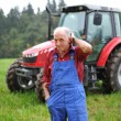 Farmer in front of his tractor — Stock Photo #56643471