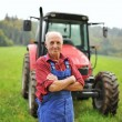Farmer in front of his tractor — Stock Photo #56643733