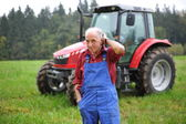 Farmer in front of his tractor — Stock Photo
