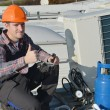 Young repairman on the roof fixing air conditioning system — Stock Photo #57239727