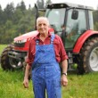 Farmer standing in front of his red tractor — Stock Photo #57239745