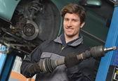 Mechanic holding car part — Stock Photo