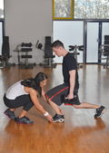 Man working out with female personal instructor — Stock Photo