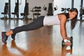 Woman doing push up exercise with dumbbell — Stock Photo