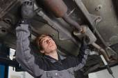 Car mechanic repairs exhaust system — Stock Photo