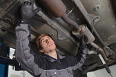 Car mechanic repairs exhaust system — 图库照片