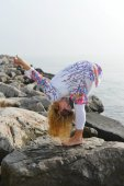 Young woman doing yoga on a rocky ocean shore — Stock Photo