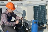 Young repairman on the roof fixing air conditioning system — Stock Photo