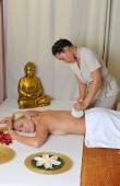 Young beautiful female receiving herbal ball massage — ストック写真