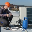 Young repairman on the roof fixing air conditioning system — Stock Photo #57240507