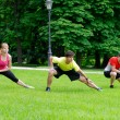 Three athletes doing stretching exercises — Stock Photo #57240695