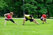 Three athletes doing stretching exercises — Stock Photo