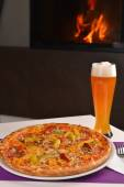 Hot pizza with a glass of cold beer — Stock Photo