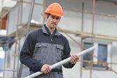 Young engineer holding blueprint — Stockfoto