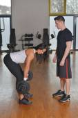 Male personal trainer assisting a woman — Stock Photo