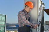 Young repairman on the roof fixing air conditioning system — Stockfoto