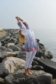 Young woman doing yoga on a rocky ocean shore — 图库照片