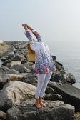 Mladá žena, která dělá jógu na skalní moře pobřeží — Stock fotografie