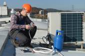Young repairman on the roof fixing air conditioning system — Fotografia Stock