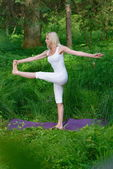 Woman practices yoga in nature — Stock Photo