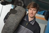 Car Mechanic And Spare Tire — Stock Photo