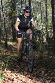Man cycling in forest — Stock Photo