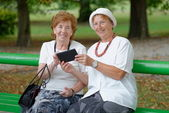 Two senior ladies reading news — Stock Photo