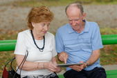 Two senior people sitting with a tablet PC — Stock Photo