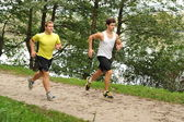 Two young athletes jogging / running in the park — Stock Photo
