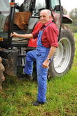 Proud farmer standing in front of his tractor — Stock Photo