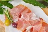 Sliced prosciutto meat — Stock Photo
